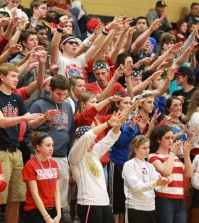 The crowd raises their arms to support FHN's boys varsirty team during a free-throw.