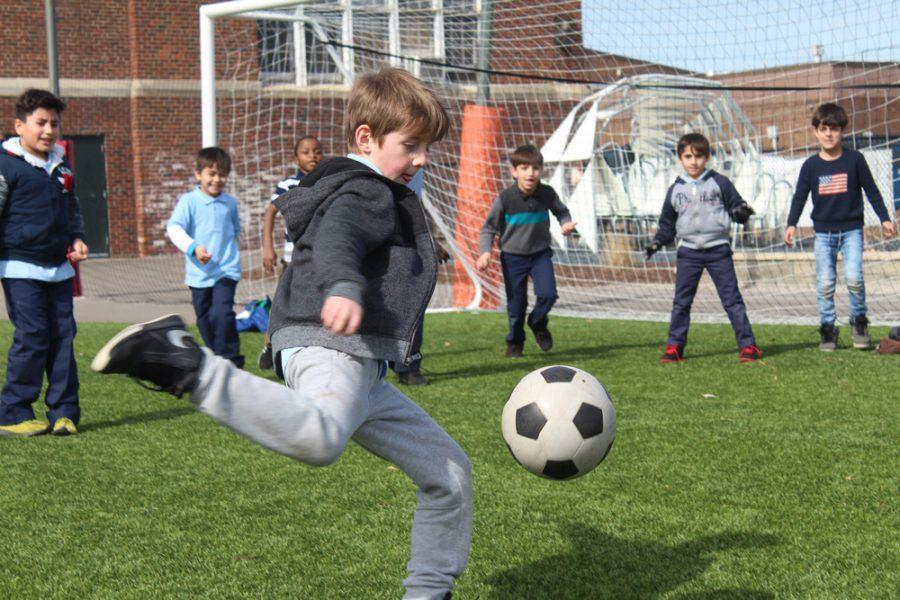A+student+plays+soccer+with+his+classmates+during+recess+outside+of+the+Nahed+Chapman+American+Academy.+The+soccer+field+the+students+play+on+was+funded+by+donors+to+the+school+in+support+of+a+turf+field.
