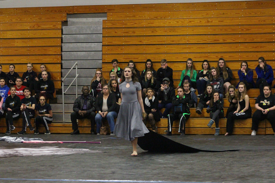 Sophomore Jacqueline Jansen pulls a tarp during the winter guard performance titled