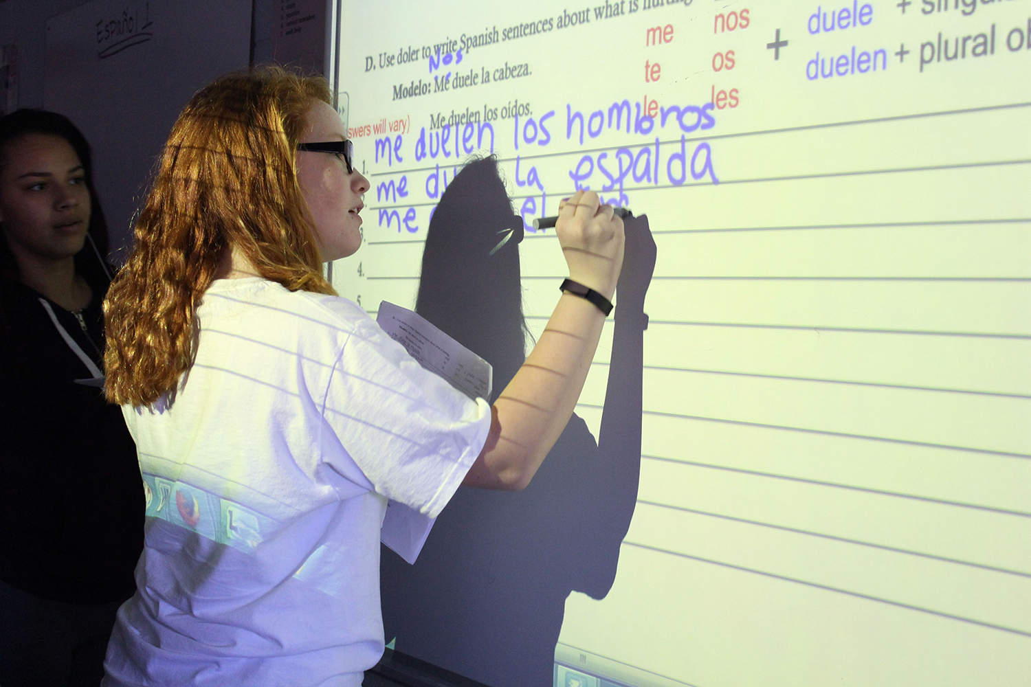 Freshman Elizabeth Cox writes a sentence in Spanish on the Smart Board while in Anelise Mossinghoff's fifth hour Spanish I class.