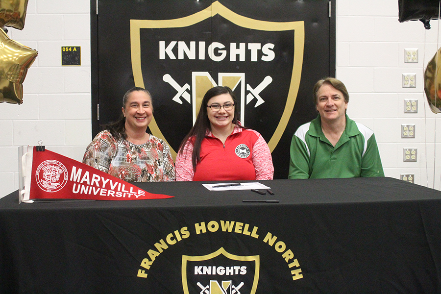 Senior Courtney Lauer, with her parents, signs with Maryville University.
