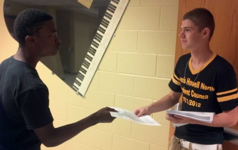 StuCo representative hands out fliers to students at meeting.