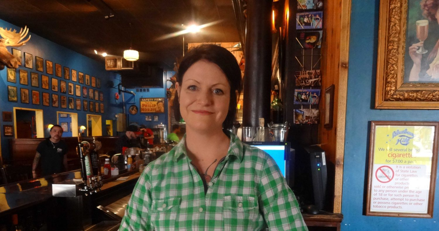 Bar Manager Becca Schock stands behind the bar waiting to serve customers.
