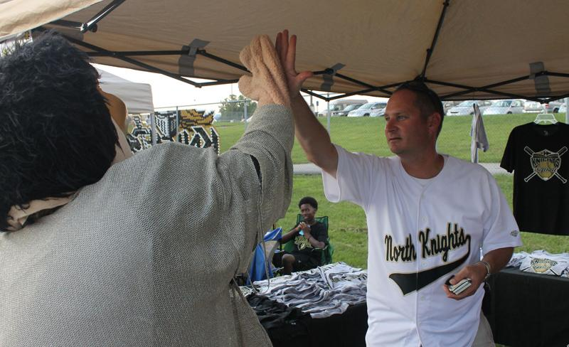 Norm high fives Mr. Janes  while he was helping sell FHN apparel at the softball booth. The softball players were also walking around the event selling lemonade. Throughout the day, Norm visited all of the booths and gave many high fives.
