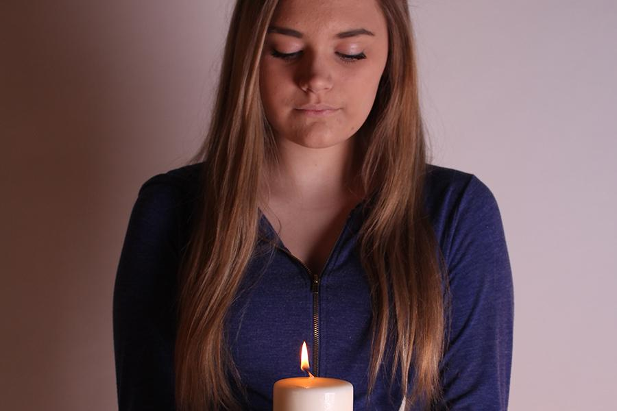 Sophomore Madison Meers holds a single lit candle to signify her life. Madison is involved with the school yearbook and works at Fazolis.