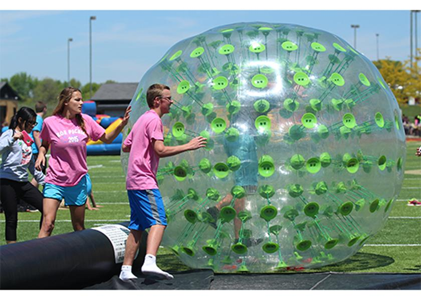 Junior KOE members Jessica Jones and Drew Lanig help students get into an inflatable ball, in which they raced down the field in. The picnic is a yearly reward with food and games, for students with good grades, being student of the week or having good attendance.  (File Photo)