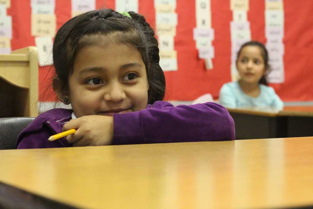 A student smiles as she looks on at the rest of her classmates. Nahed Chapman's enrollment has doubled since the beginning of the school year, leading to a rise in the student to teacher ratio.