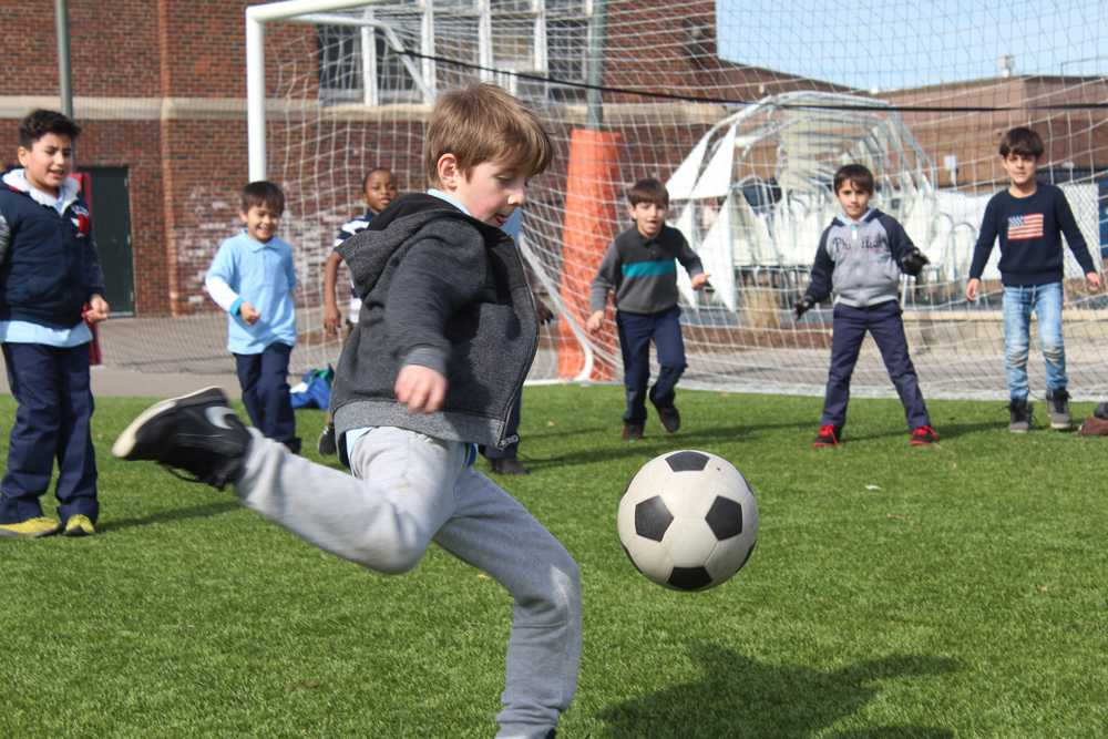 A student plays soccer with his classmates during recess outside of the Nahed Chapman American Academy. The soccer field the students play on was funded by donors to the school in support of a turf field.