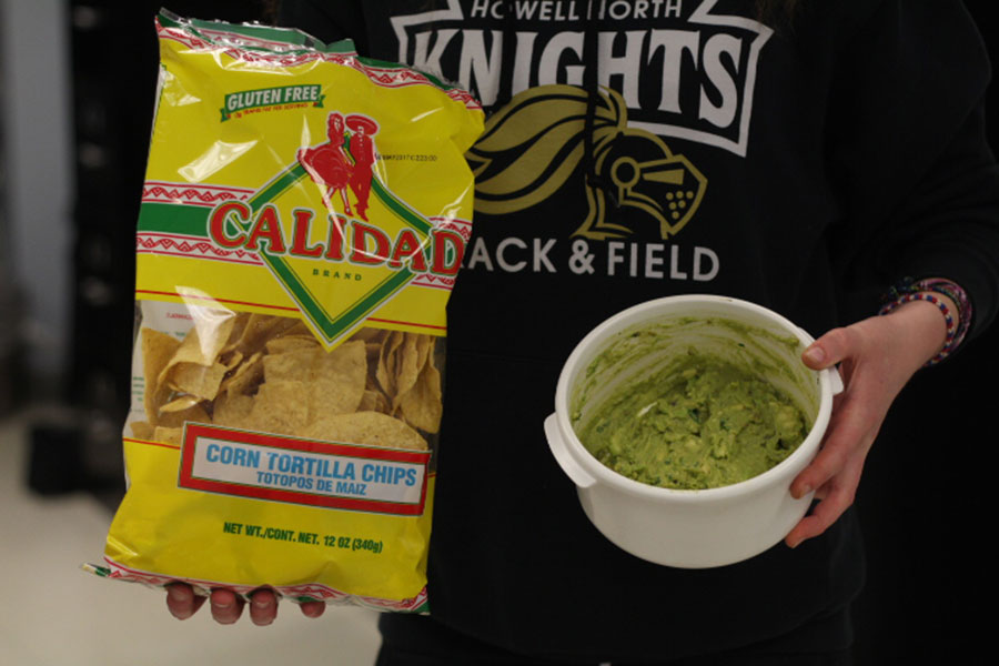 The completed guacamole is held next to a bag of tortilla chips.