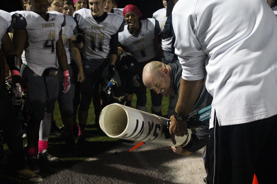 Coach Mike Bevill cuts the pipe, while head coach Brett Bevill holds it in place, after the Knights defeat Washington High School 41-25.