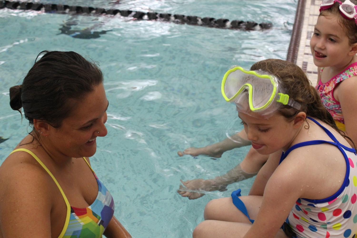 Swim+instructor+Emily+Kolb+talks+to+her+students+about+the+new+skills+they+are+going+to+be+taught+during+that+night%27s+class.+Kolb%E2%80%99s+students+learn+how+to+float+on+their+back+and+other+basic+swim+strokes.+