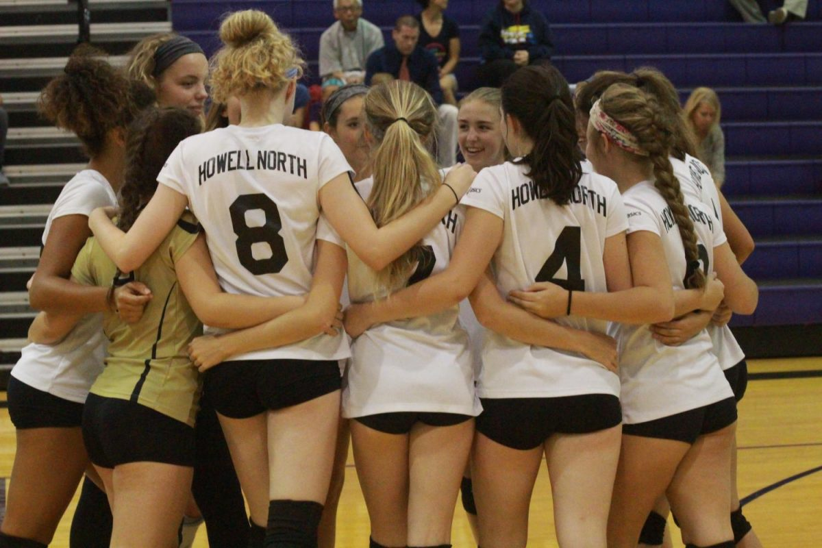 The Varsity Girls Volleyball team huddles before beginning their first match of the game.