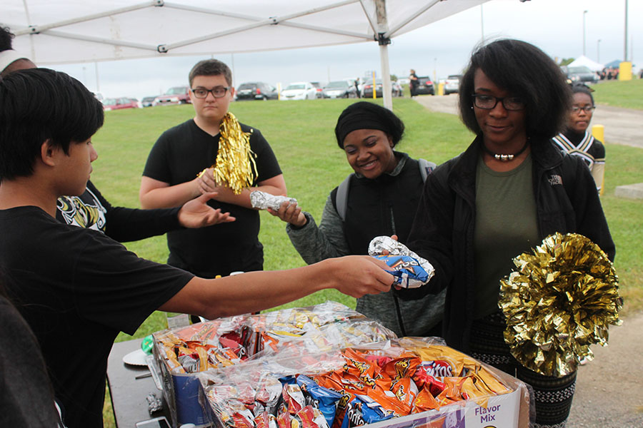 A+Student+Council+member+hands+chips+to+students+during+the+Homecoming+Tailgate.+