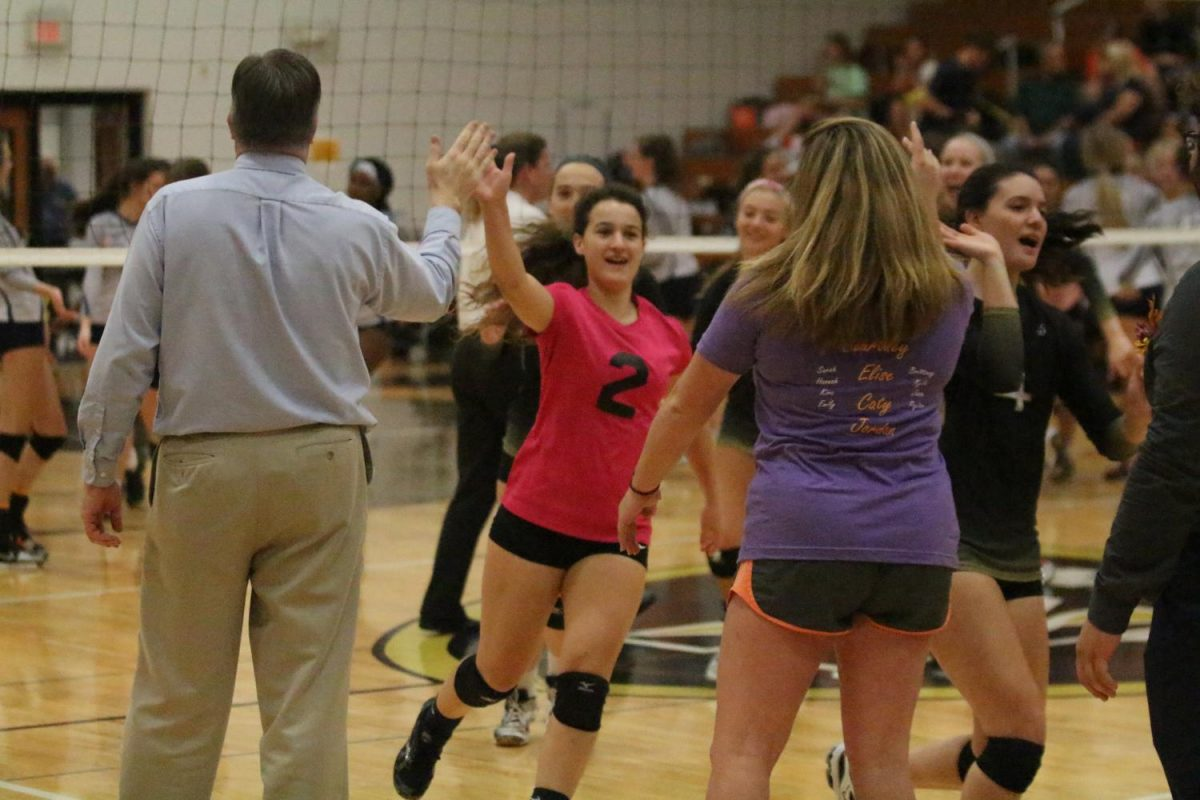 Junior Sarah Zimmerman high fives her coach and teammates before the match.