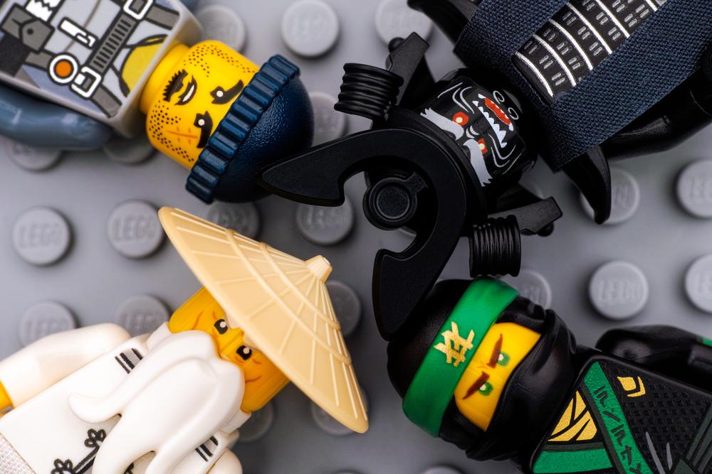 Tambov, Russian Federation - August 19, 2017 Four Lego Ninjago Movie minifigures - The Green Ninja, Wu, Garmadon and Charlie - on gray baseplate background. (Studio shot)