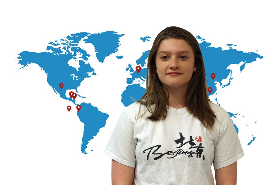 "Junior Aslee Addison poses in front of a map with pinpoints of several places she's visited around the world. With Addison regularly traveling, she has become familiar with the countries and think of it as a ""home away from home."""