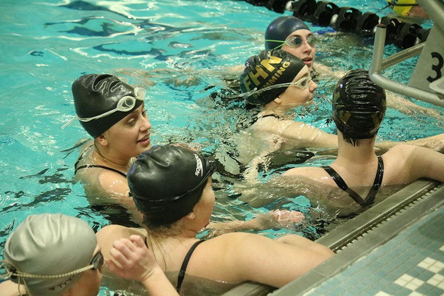 The Howell North Lady Knights girls swimming team huddles in the swimming pool