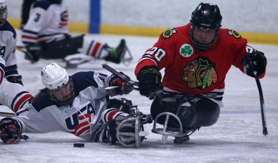 Kelsey DiClaudio goes for a tackle against a Chicago Blackhawk player.  DiClaudio is one of three players from Missouri on the team. She was born with a spinal cord injury which caused her to eventually be in a wheel chair.