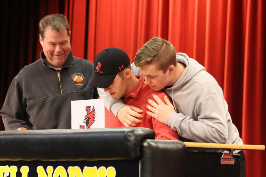 Connor Gallagher signs for William Jewell College with his brother Evan watching over his shoulder.