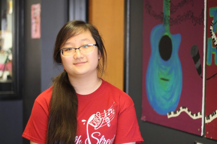 Sophomore Jena Pae poses in the Learning Commons as she wears a shirt with the winning logo she designed for Coffeehouse. Pae entered the Coffeehouse contest with a drawing that took her over four hours. She studied different fonts, chose her favorite and then practiced that style.