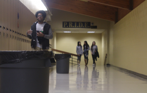 Students pass the trash cans that sit near the butterfly hallway. The hallway is notorious for constantly having trash cans sitting out to catch the water from the leaks. Leaks have been less frequent since the skylights in the butterfly hallway were removed.