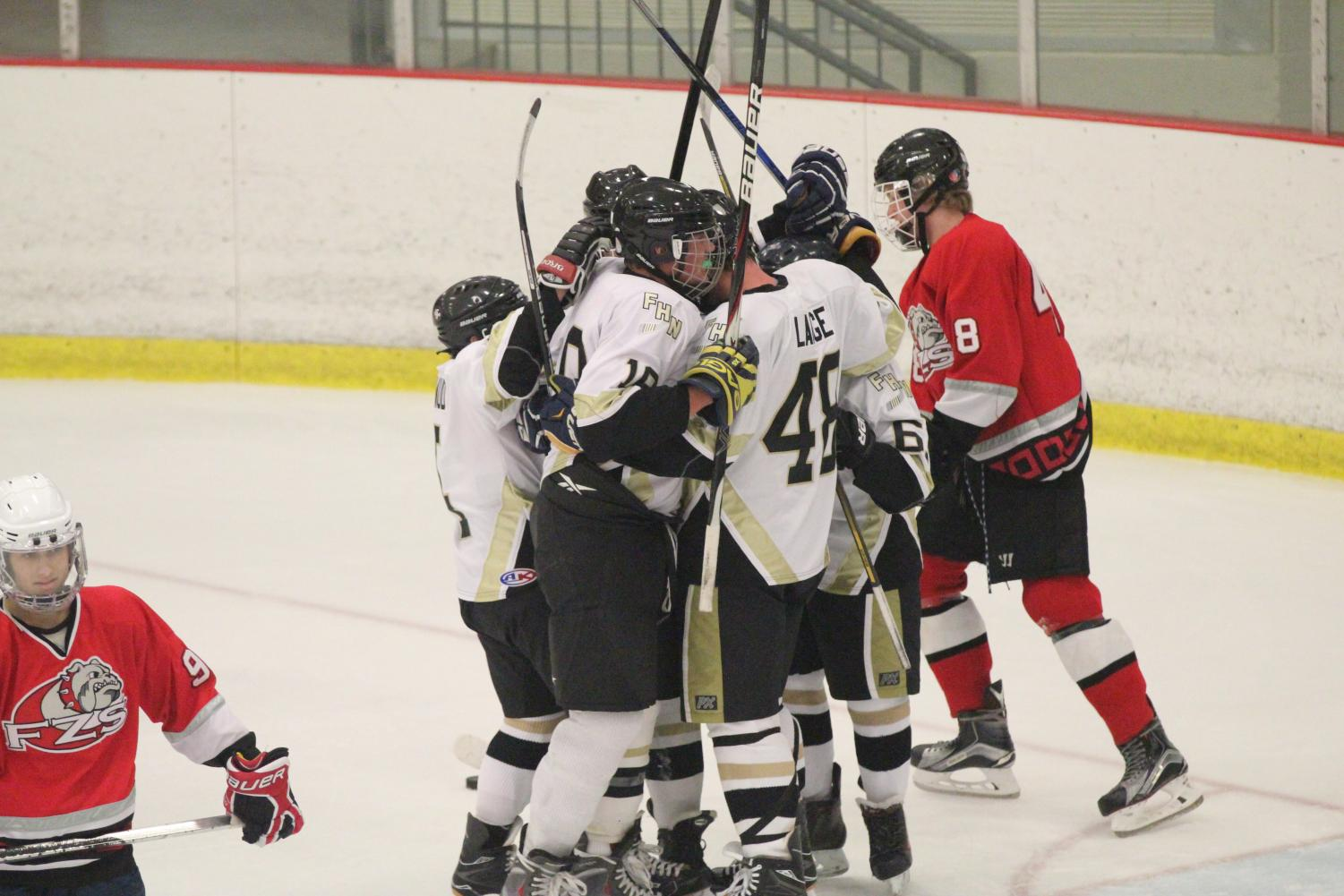 The varsity Knights hockey team celebrates a goal vs. Fort Zumwalt South