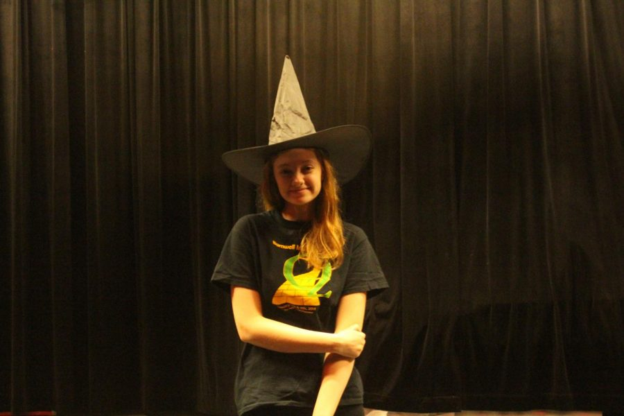 """Senior Delaney Echelmeyer poses on the FHN stage in her witch hat. She has been involved in theatre for seven years. """"My favorite part about performing is how a whole ensemble of people from such different lives can come together and create something incredible,"""" Echelmeyer said."""