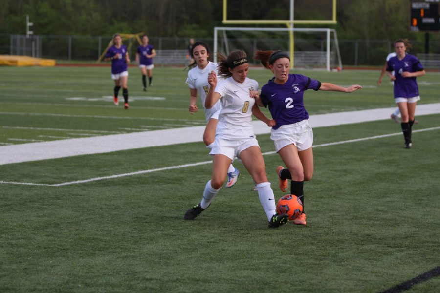 Senior Madelynn Wood challenges a FZW defender on 4/13 in a varsity soccer match at Howell North.