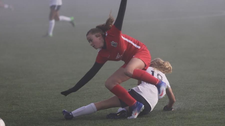 Freshman+Julia+Kristensen+slides+in+on+an+attacker+in+a+club+match.