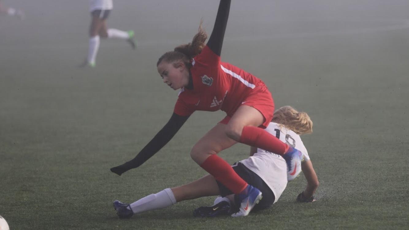 Freshman Julia Kristensen slides in on an attacker in a club match.