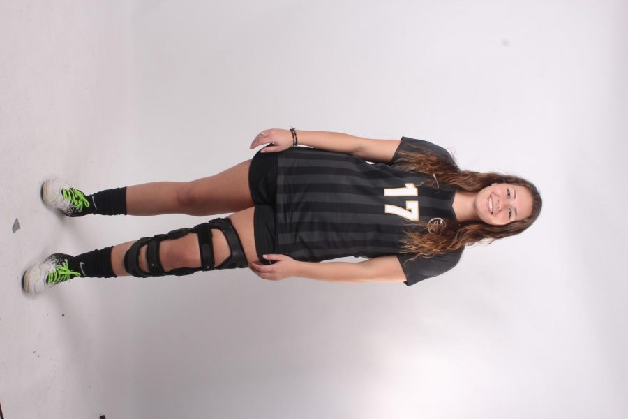 Senior Caty Arnold poses in her soccer uniform and leg brace. Arnold has been playing soccer and volleyball for FHN for all four years.