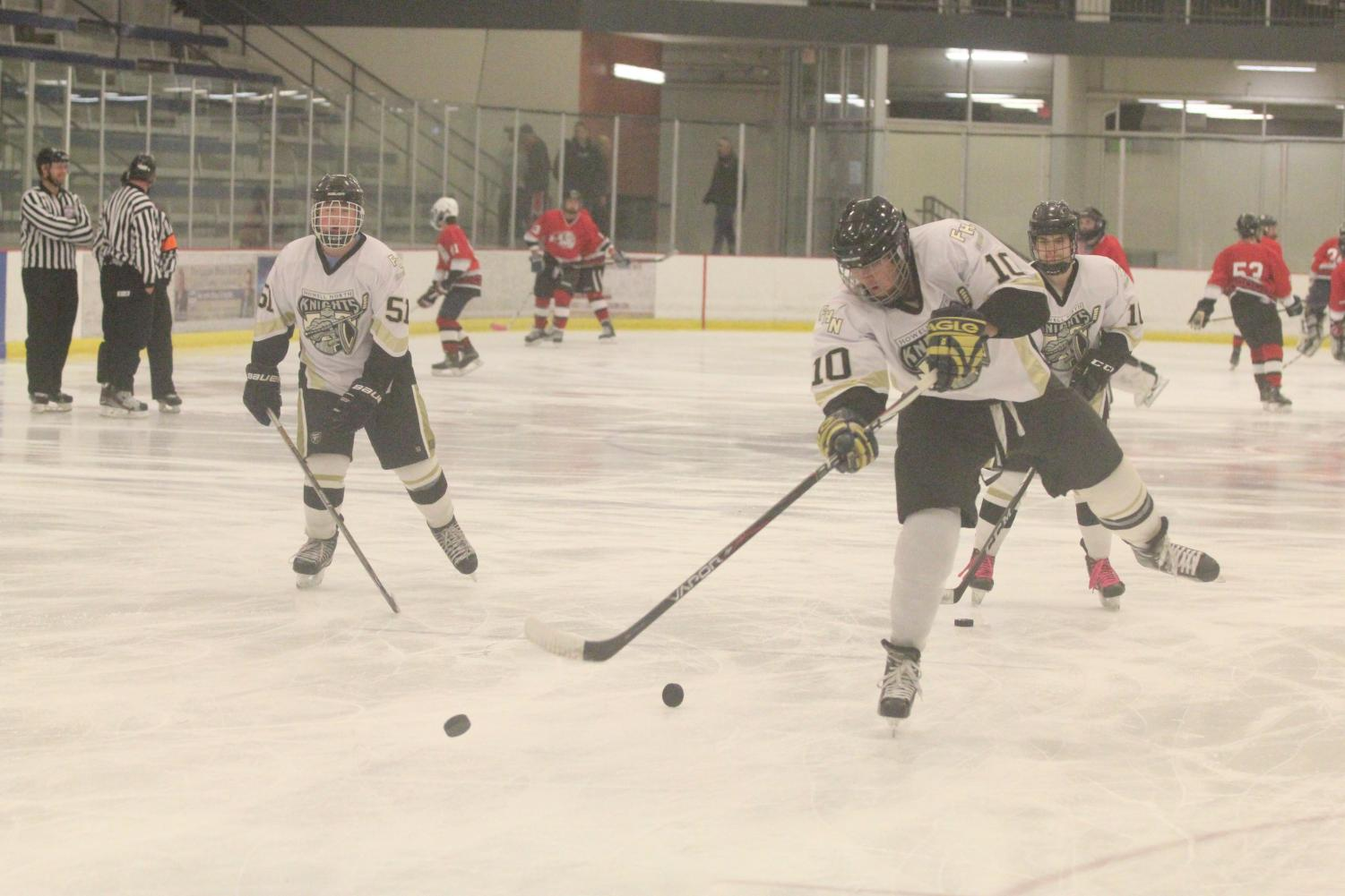 Senior Kurt Springli (#10) takes a shot on goal with fellow senior Jacob Casey watching in the background in warmups ahead of FHN's varsity hockey game vs. FZS on 11/10.