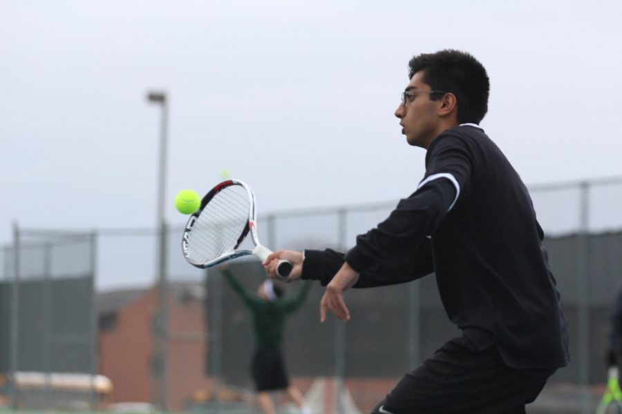 Senior Sachin Milli returns a serve in a varsity tennis match on  3/31 vs. FZN.