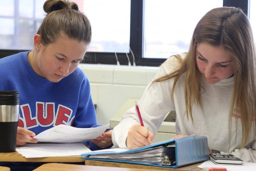 Junior Maddie Battles  (right) works on homework during homeroom. At the beginning of the year, everyone was assigned a homeroom based on their last name and grade. Homeroom allows students to work on homework and study for test and quizzes on collaboration days.