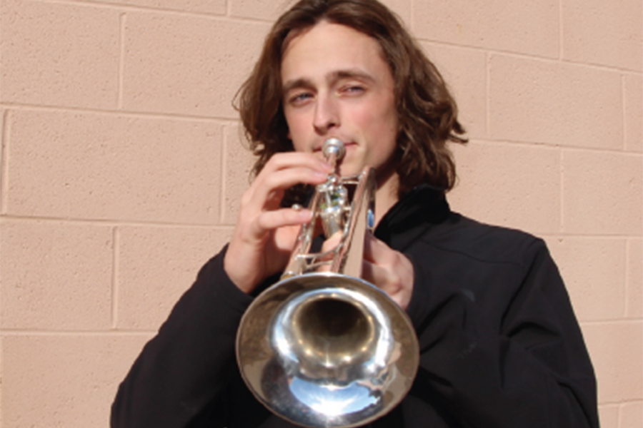 """Senior Ian Perry plays his trumpet. Perry was accepted into a drum corps in January. """"My first thought when I saw I was accepted was just wow,"""" Perry said."""