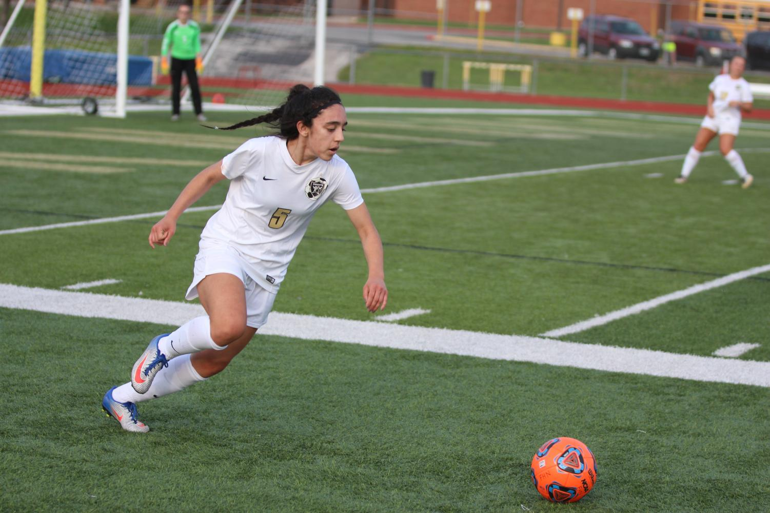 Sophomore wing back Lauren Shah prepares to knock the ball up the field in a match with FZW on 4/13.