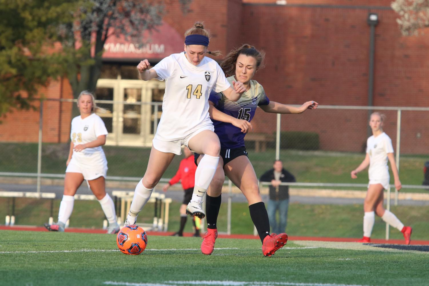 Senior Megan Crain takes on Troy defender Morgan Bova in a GAC South contest on 4/17 at Francis Howell North. The Trojans won the game by a score of 2-1.