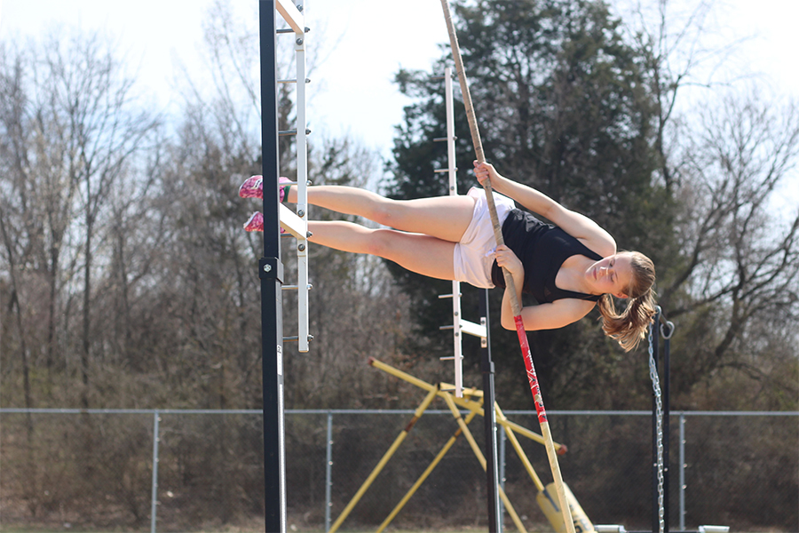 Junior Natalie Archer vaults through the air with her vaulting stick. Archer has been pole vaulting for the past three years. She made the switch to pole vaulting after leaving gymnastics due to injury.