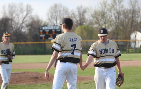 Seniors Sam Grace and Noah Pingel give each other a high-five as they head back to the dugout after the top of the fifth inning on 4/24 vs. Holt.