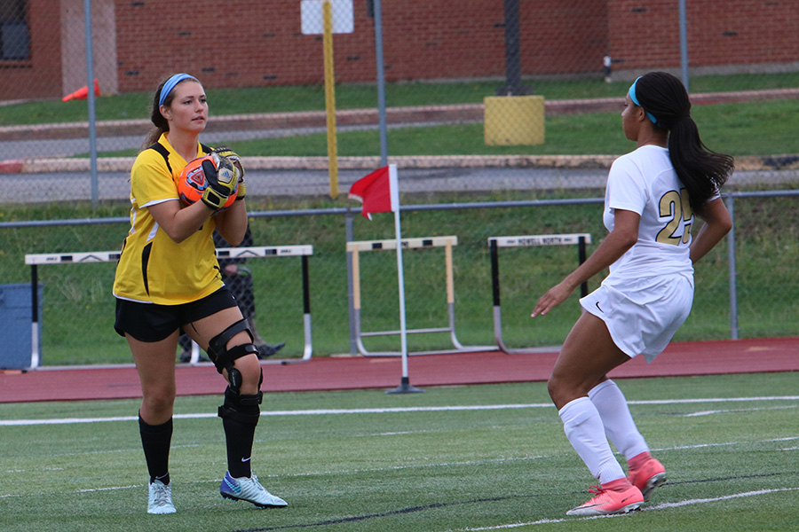 Senior goalkeeper Caty Arnold collects the ball with junior Karen Pete watching vs. Marquette on 5/3.