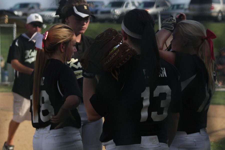 The Varsity Softball team gather together to talk strategy before heading onto the field.