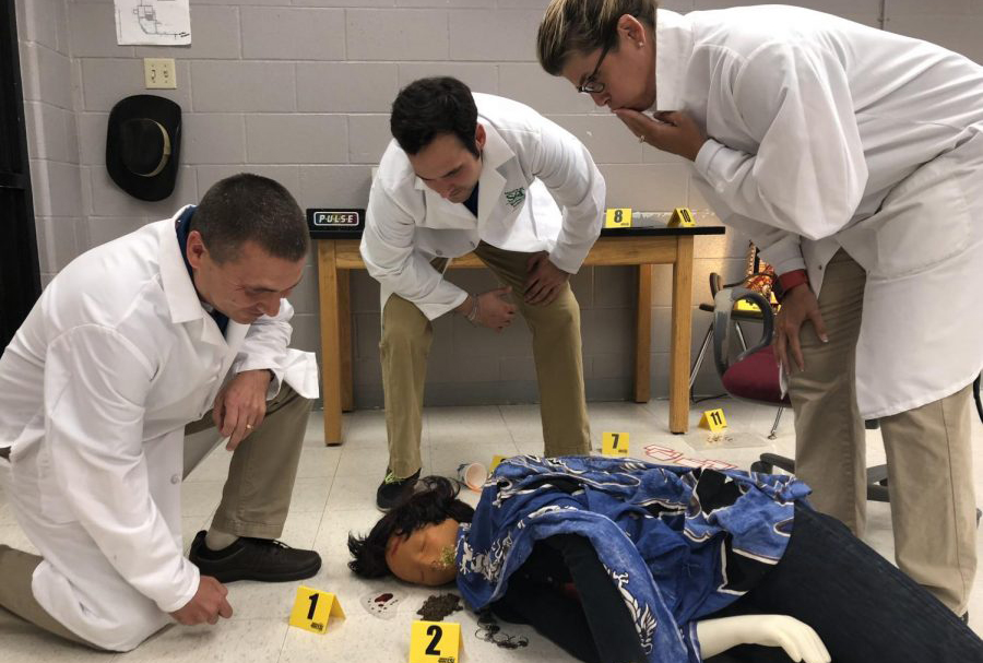 (From left) Chris Dalton, Matt Howard and Dawn Hahn investigate the crime scene of Anna Garcia, a person of study in Principals of Biomedical Science. All three teachers have taken on new PLTW classes this year.