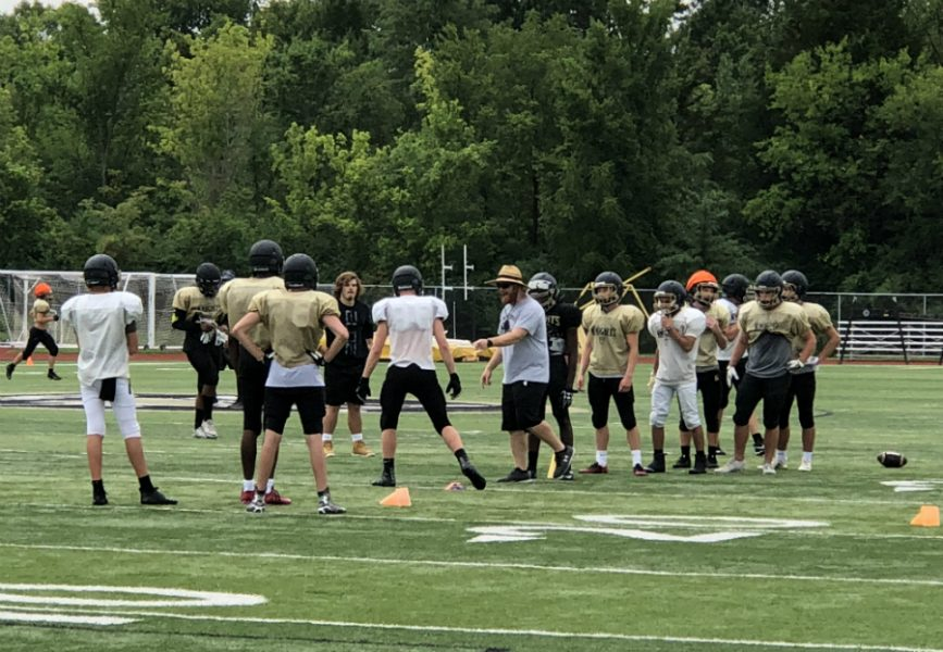 Football Head Coach Brett Bevill, instructs his athletes in a practice on August 15.