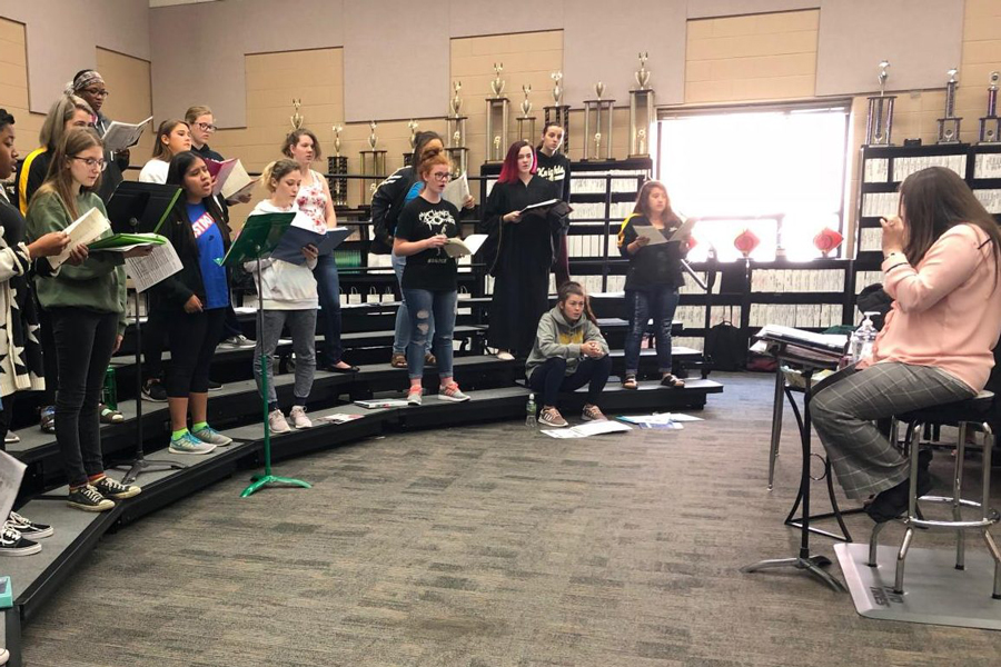 Bella Voce ladies read their music while watching Jennifer Crane for cut-offs. This choir rehearses during fifth hour everyday. Their first concert is on Nov. 20.