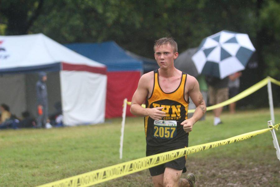 Senior Ben Ludwig runs through the mud at the Forest Park meet.