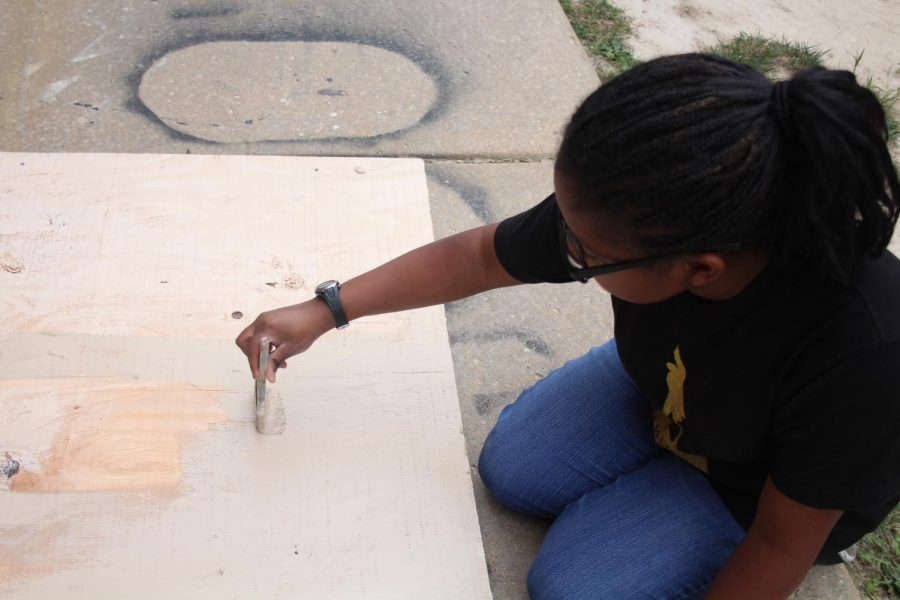 """Sophomore Carolyn Green paints a portion of the set for the upcoming play """"You Can't Take it With You"""". The play highlights two families, one proper and the other disfunctional, and the struggle of love and acceptance. """"You Can't Take it With You"""" is scheduled for Oct. 25-27 from 7pm to 9:30pm."""