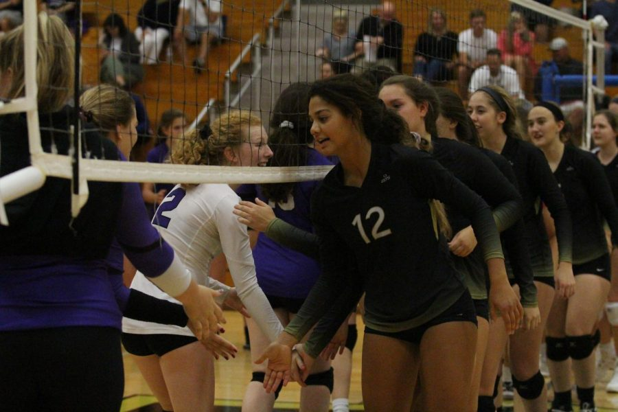 Senior Payton Stephenson high fives the opposing team before a match against Fort Zumwalt West. Stephenson is one of the two members that were voted to be team captains of the team.