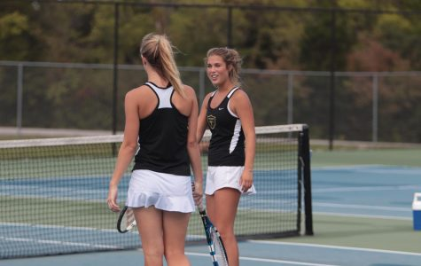 Senior Maggie Majesky talks with doubles teammate during a match against Howell on 9-21.