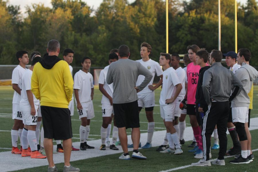 Coaches+Larry+Scheller+%5Bin+yellow%5D+and+Zach+Fettig+talk+to+the+soccer+team+before+playing+against+CBC
