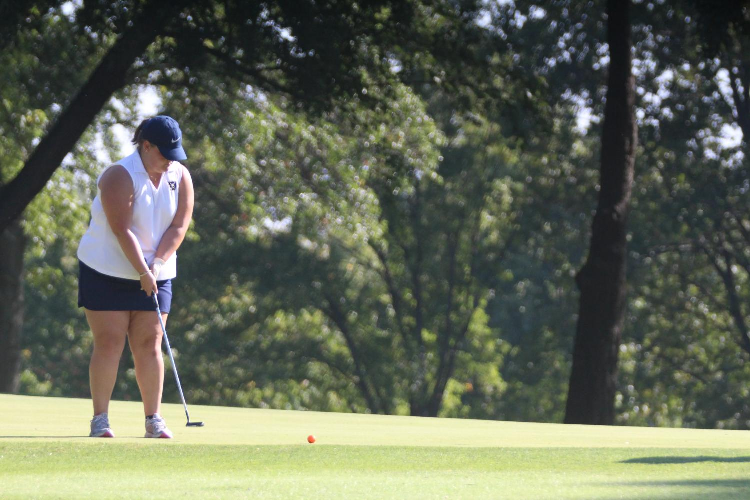 Senior Sarah LaLonde putts the ball into the hole.
